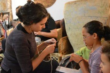 Woman teaching girl to knit