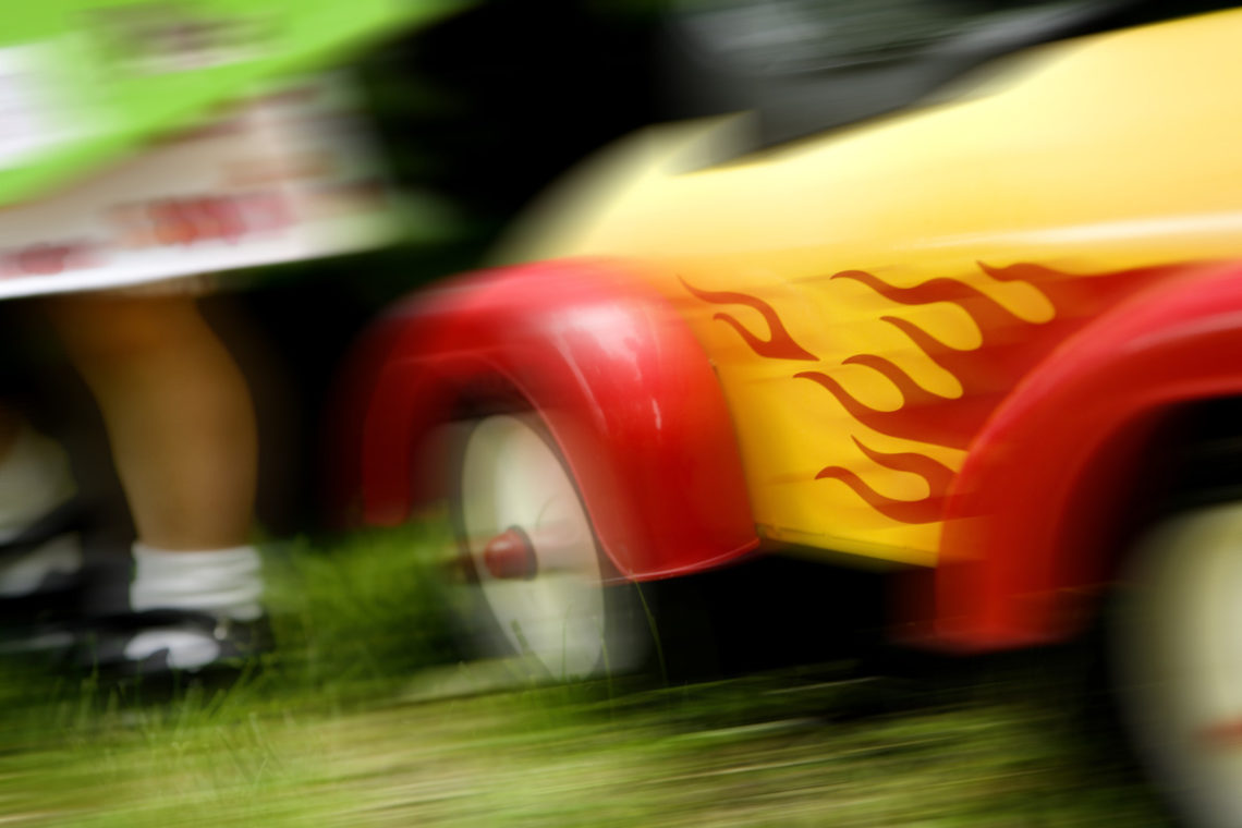Blurred image of child's yellow and red ride-in car