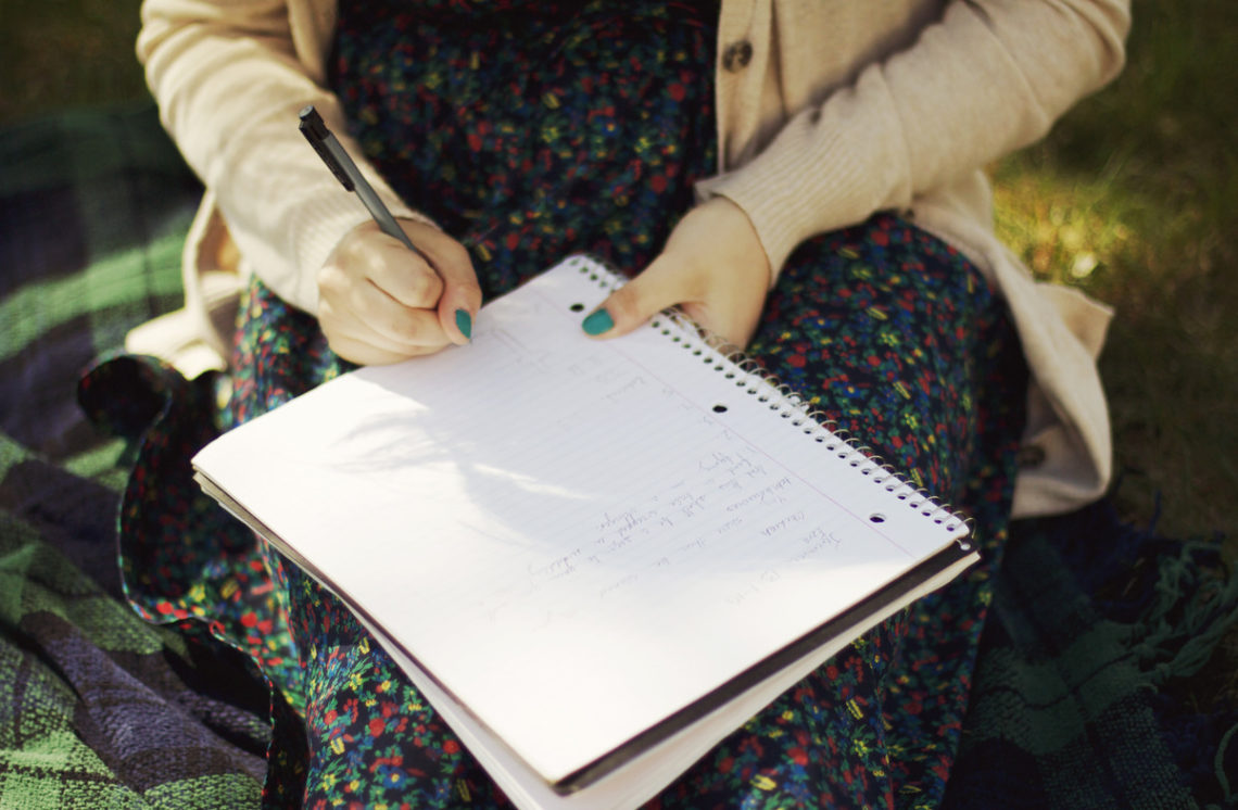 Image of woman writing in journal on her lap