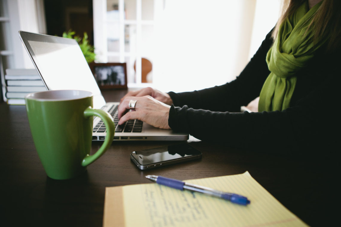 Image of woman using laptop and a green mug