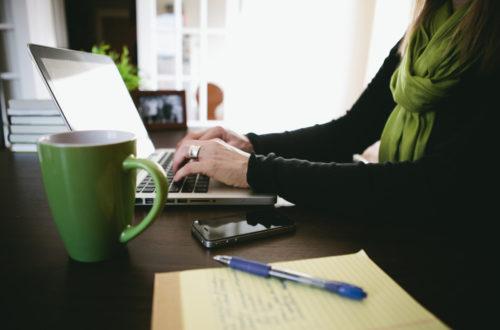 Image of woman using laptop and a green mug