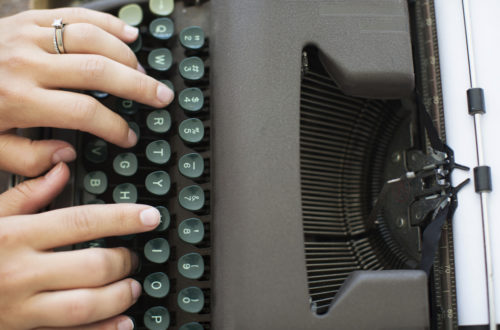 Image of hands and vintage typewriter keys