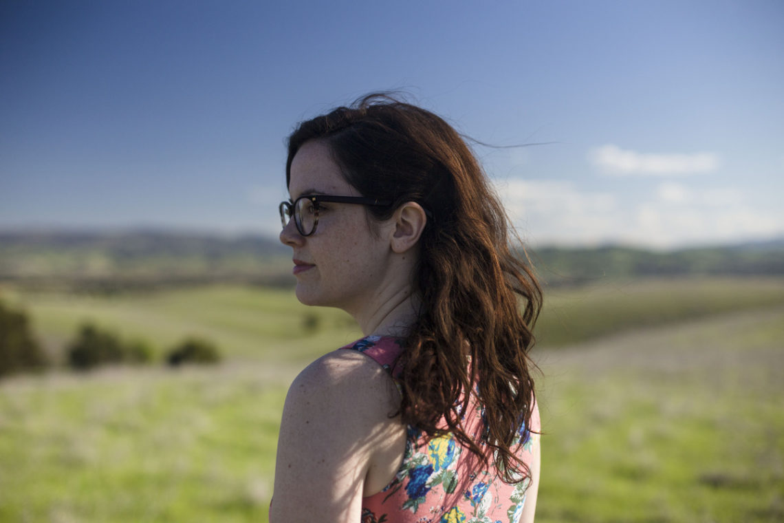 Image of young woman standing in field looking over shoulder