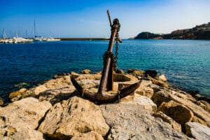 Large anchor on rocky shore