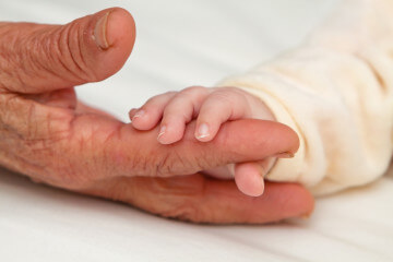 Closeup image of baby holding Great Grandma's fingers