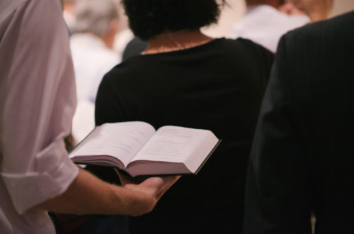 Image of man holding hymnbook