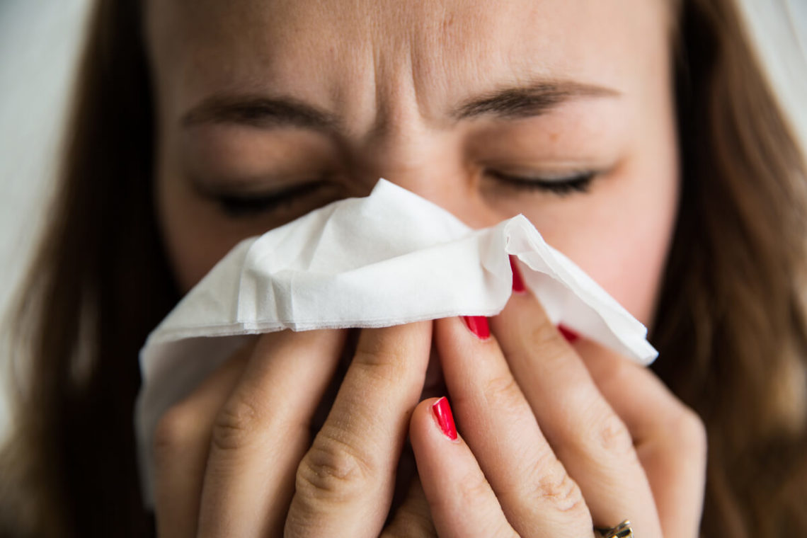 Image of woman holding tissue to nose