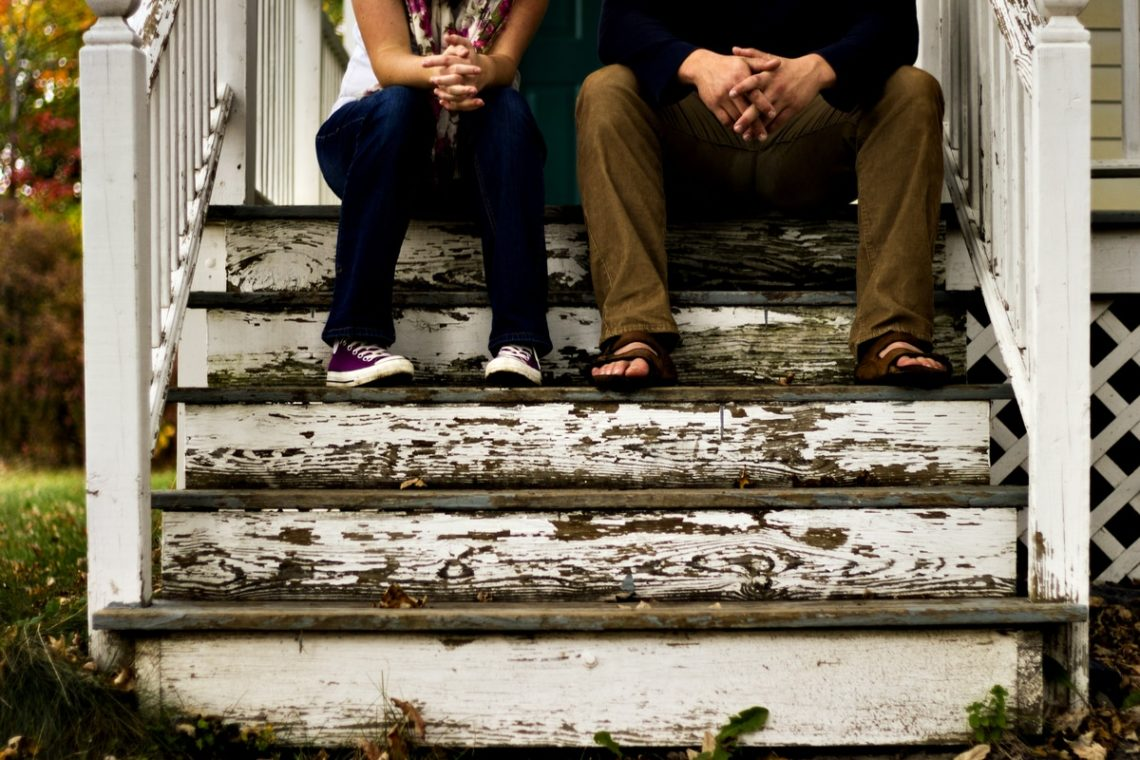 man_and_woman_sitting_on_wooden_steps