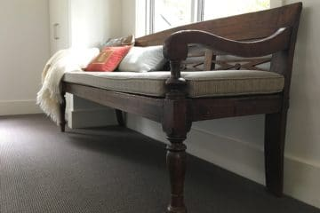 Old mahogany bench with cushions and throw