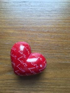 Small red heart-shaped paperweight inscribed all over with the word 'Love'