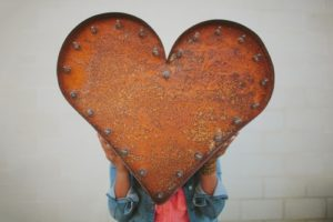 Girl holding large rusty metal heart