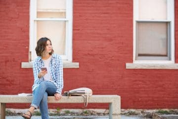 Young woman sitting on concrete bench, waiting