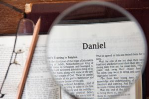 Bible with magnifying glass highlighting title page of Daniel