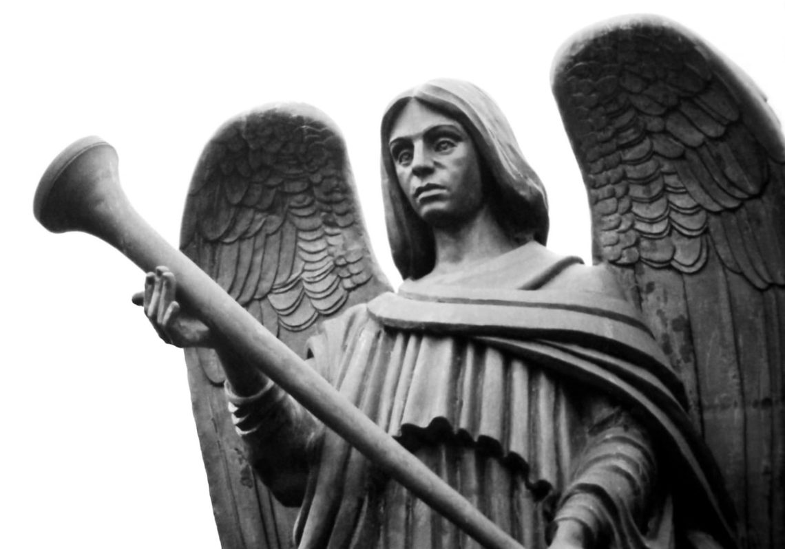 Stone statue of powerful angel with trumpet